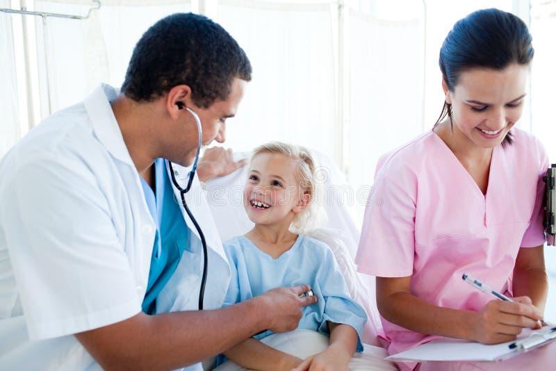 Un doctor y una enfermera que examinan a un paciente del niño imagen de archivo libre de regalías