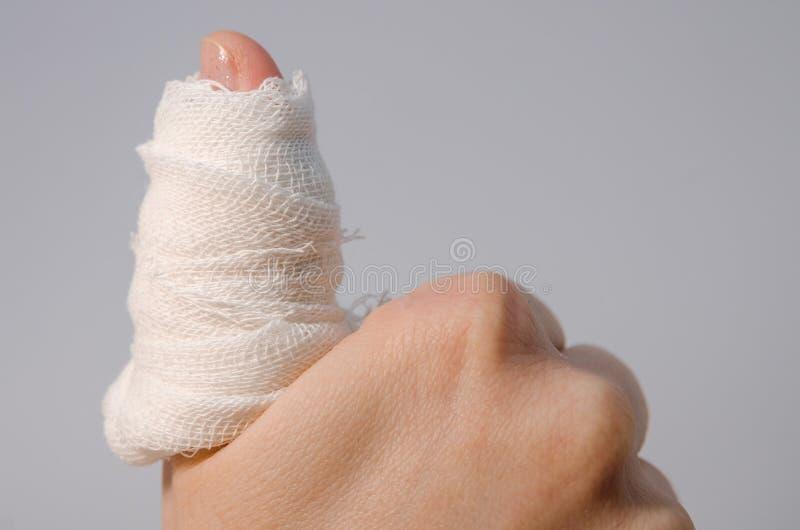 Un doigt dans le bandage ensanglanté image libre de droits
