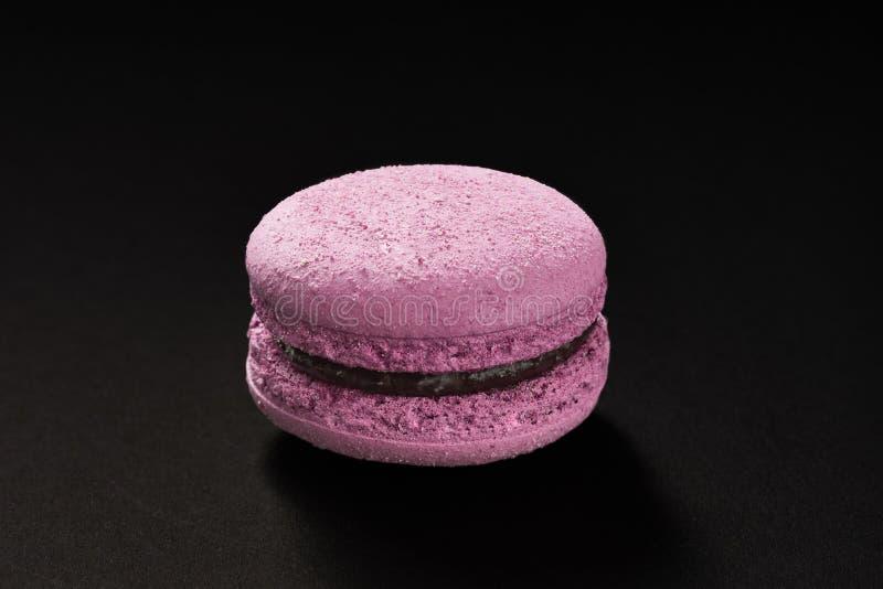 Un dolce di colore della viola dei maccheroni Maccherone delizioso del ribes isolato su fondo nero Biscotto dolce francese fotografia stock