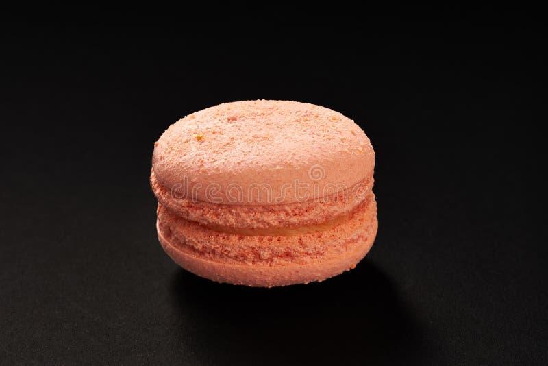 Un dolce di colore peachy dei maccheroni Maccherone delizioso isolato su fondo nero Biscotto dolce francese immagine stock