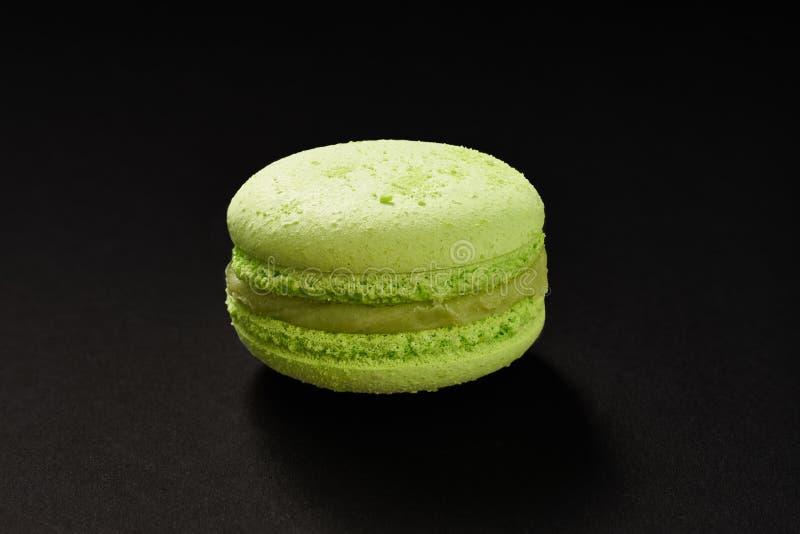 Un dolce di colore verde dei maccheroni Maccherone delizioso del pistacchio isolato su fondo nero Biscotto dolce francese fotografia stock