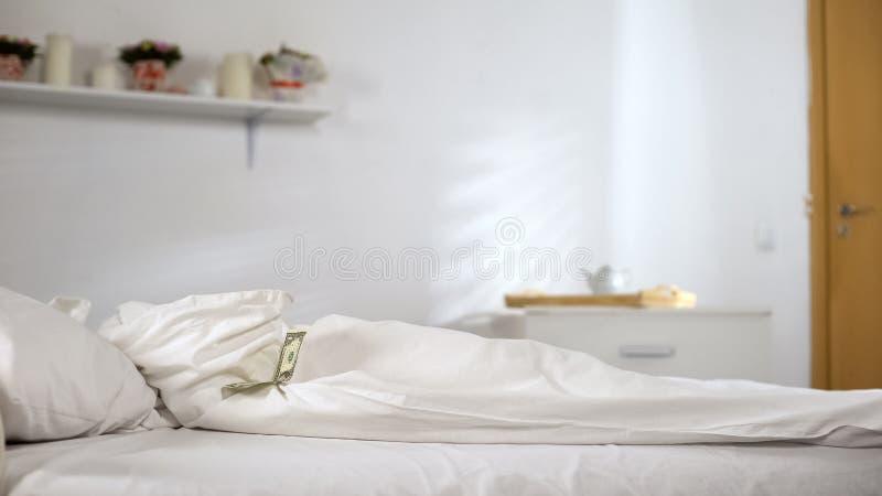 Un dollar se trouvant sur le lit dans la chambre d'hôtel, astuces des visiteurs, service de nettoyage photos libres de droits