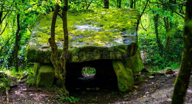 Un dolmen o una tavola-pietra magico coperta da muschio nella foresta russa della montagna fotografie stock libere da diritti