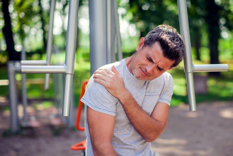 Un dolore di sensibilità dell'uomo nella sua spalla durante lo sport e allenamento nella t immagine stock