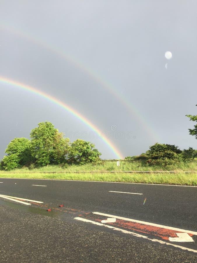 Un doppio arcobaleno che si piega gli alberi fotografia stock