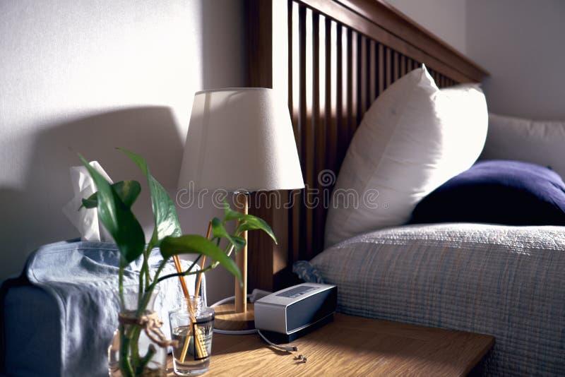 Un dormitorio con las almohadas, lámpara caja del tejido, florero, defuser, y speake portátil encendido con la luz caliente del s fotografía de archivo libre de regalías
