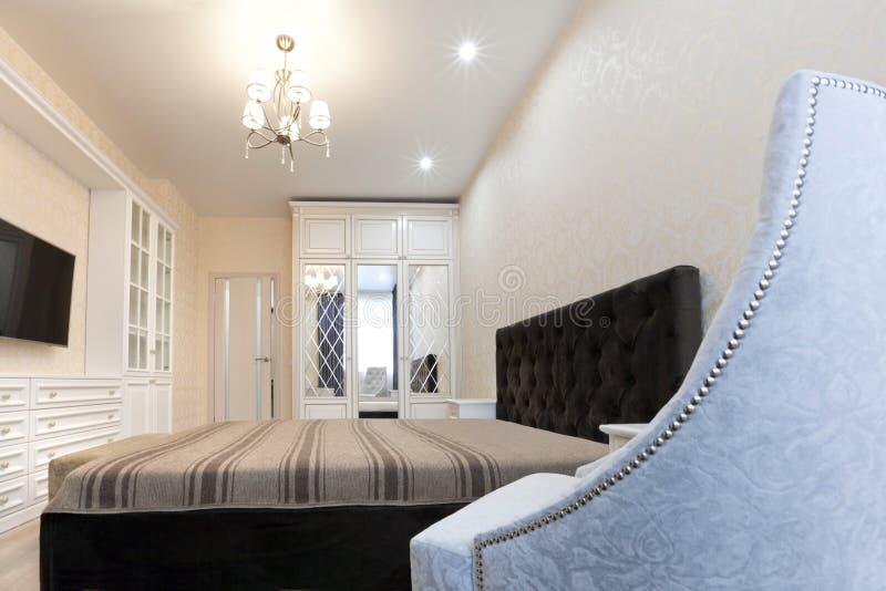 Un Dormitorio En Colores Claros Con Una Cama Oscura Y Una Silla ...