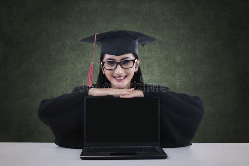 Un dottorando con il computer portatile dello schermo in bianco immagini stock
