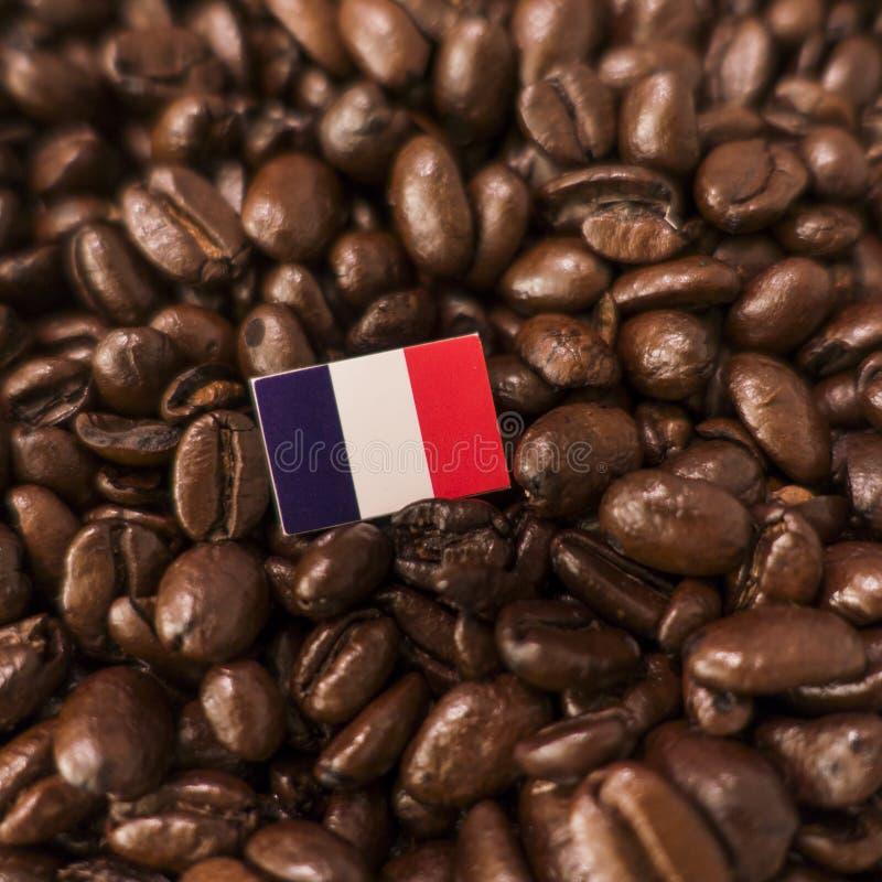 Un drapeau français placé au-dessus des grains de café rôtis image stock