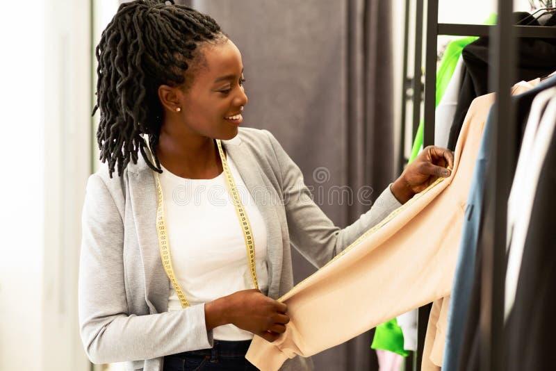 Un Dressmaker Sorridente Che Guarda Una Nuova Raccolta Di Abiti In Showroom fotografie stock libere da diritti