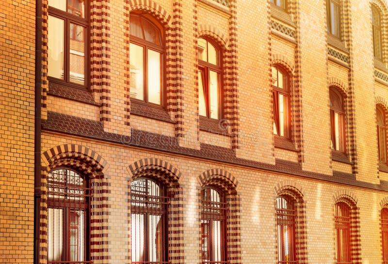 Un edificio de ladrillo con las ventanas brillantes en la puesta del sol, luz del sol hermosa reflejó del vidrio, la vieja arquit imagen de archivo