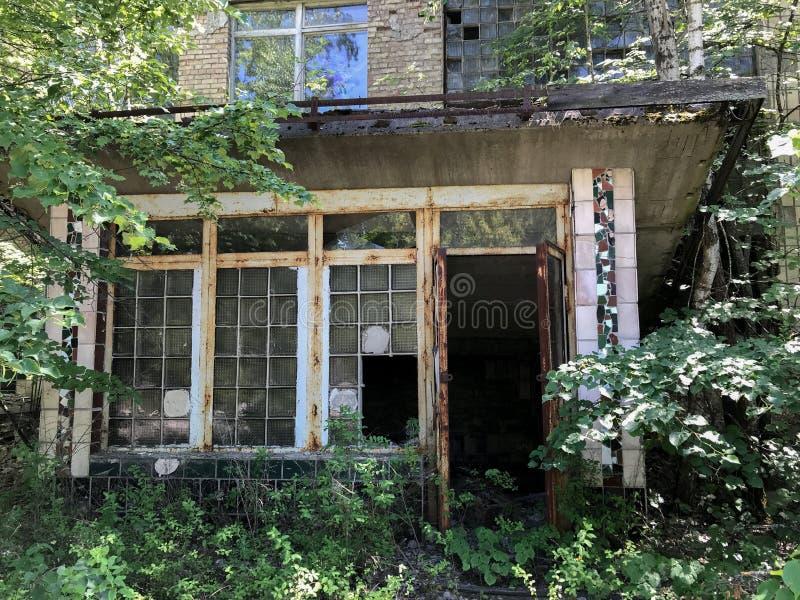 Un edificio viejo, abandonado en Pripyat, Ucrania ha roto las ventanas y los árboles que crecían a través de él después de la eva imagen de archivo libre de regalías