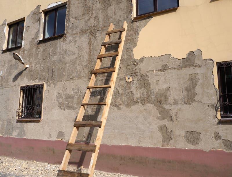 Un edificio viejo con la fachada dañada con la escalera de madera por la pared imagenes de archivo