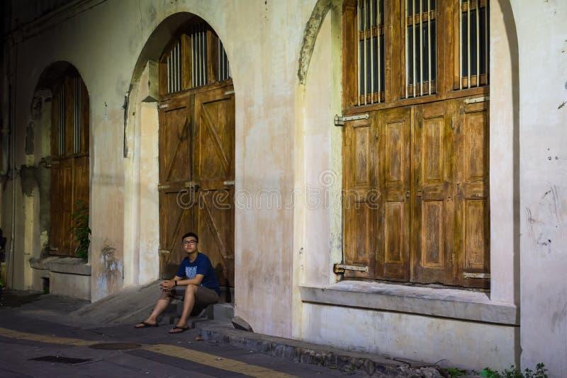 Un edificio viejo es uno del patrimonio cultural de los edificios viejos se han restaurado que Un hombre se está sentando delante fotografía de archivo libre de regalías