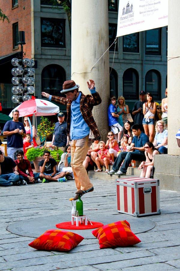 Balanzas del ejecutante de la calle encima de una botella de vino. imágenes de archivo libres de regalías