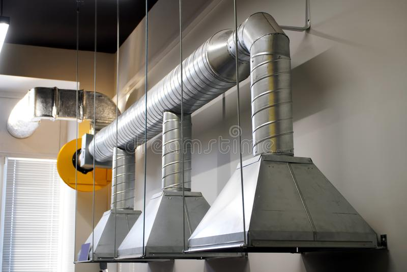 Un ejemplo de instalar la ventilación de extractor sobre un lugar de trabajo en un área industrial foto de archivo