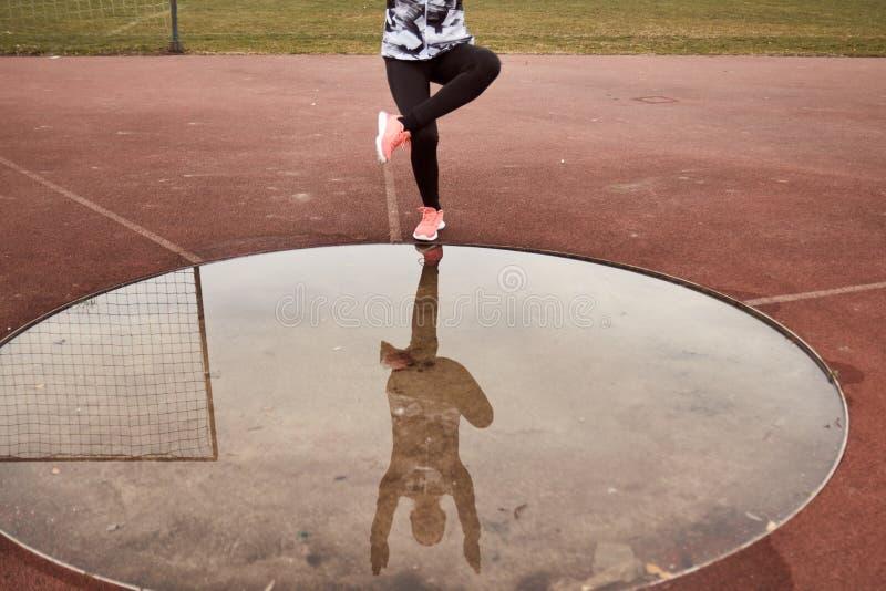 Un ejercicio reconocible de la persona, deporte viste, las medias, reflexión en agua, posición en cuclillas del charco de la Solo imagen de archivo