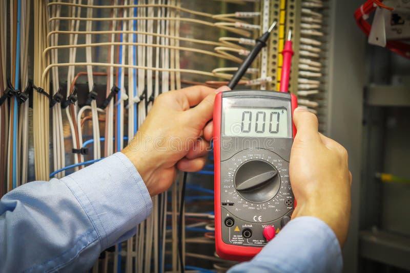 Un electricista con el primer del multímetro Manos del técnico con macro del instrumento de medida fotografía de archivo libre de regalías