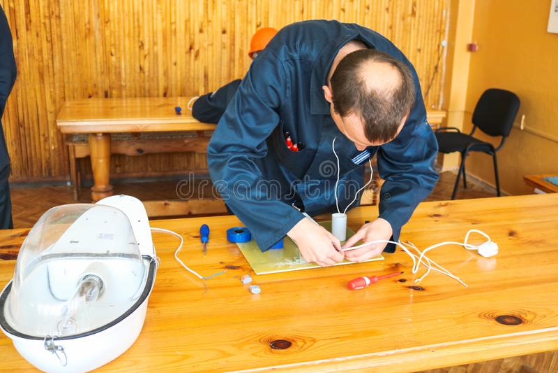 Un electricista del hombre que trabaja trabajos, recoge el circuito eléctrico de una lámpara de calle blanca grande con los alamb imagen de archivo