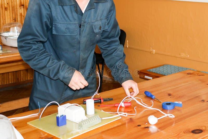 Un electricista del hombre que trabaja trabajos, recoge el circuito eléctrico de una lámpara de calle blanca grande con los alamb fotografía de archivo