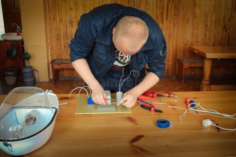 Un elettricista dell'uomo che lavora gli impianti, raccoglie il circuito elettrico di grande lampada di via bianca con i cavi, un fotografie stock libere da diritti