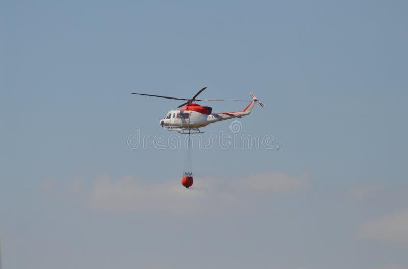 Un elicottero che prende acqua ad un fuoco di Bush fotografia stock libera da diritti