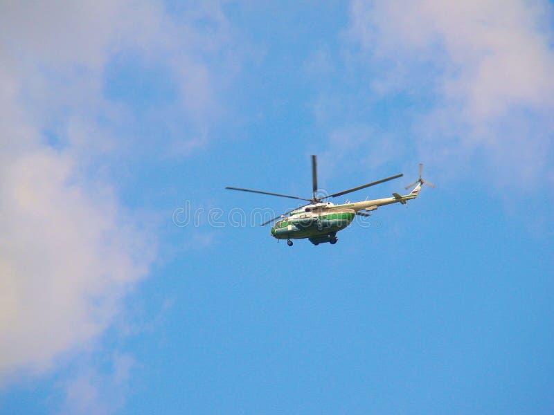 Un elicottero nel cielo blu fra le nuvole fotografia stock