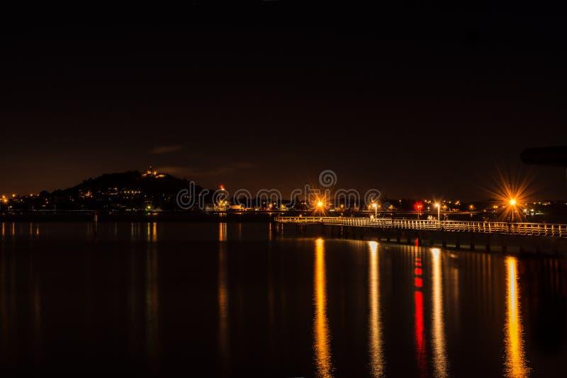 Un embarcadero en la noche: luces de la l?mpara, un grupo borroso de pescadores y una silueta distante del soporte Victoria imágenes de archivo libres de regalías
