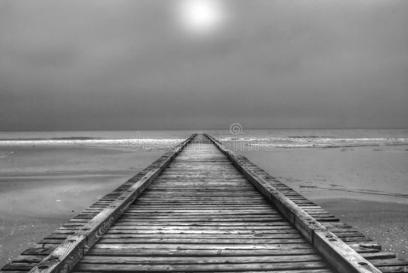 Un embarcadero viejo en el mar al día oscuro y tempestuoso fotos de archivo libres de regalías