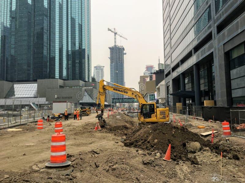 Un emplazamiento de la obra grande en Edmonton céntrica, Alberta con un excavador y los trabajadores de construcción que continúa imagen de archivo
