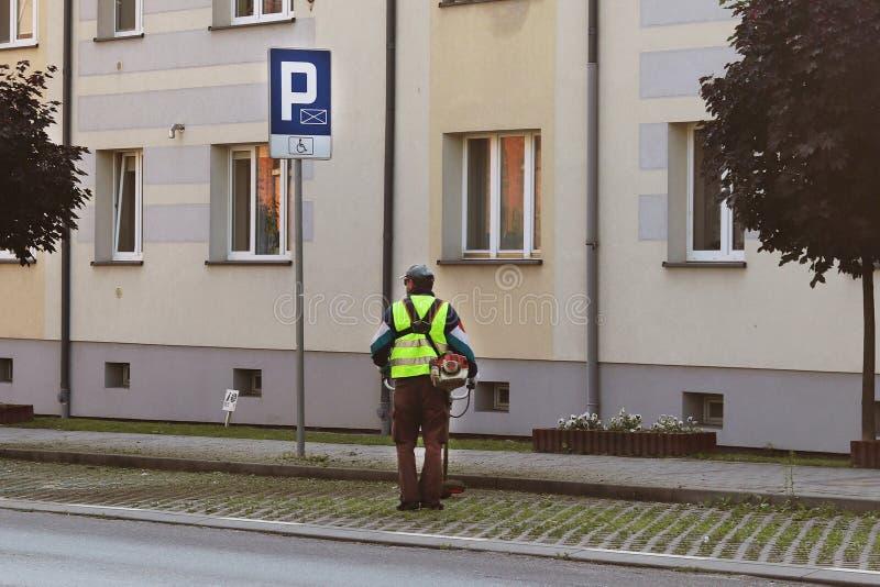 Un empleado del servicio municipal de la ciudad quita el territorio Refinamiento del área alrededor de la casa Siega de la hierba foto de archivo libre de regalías