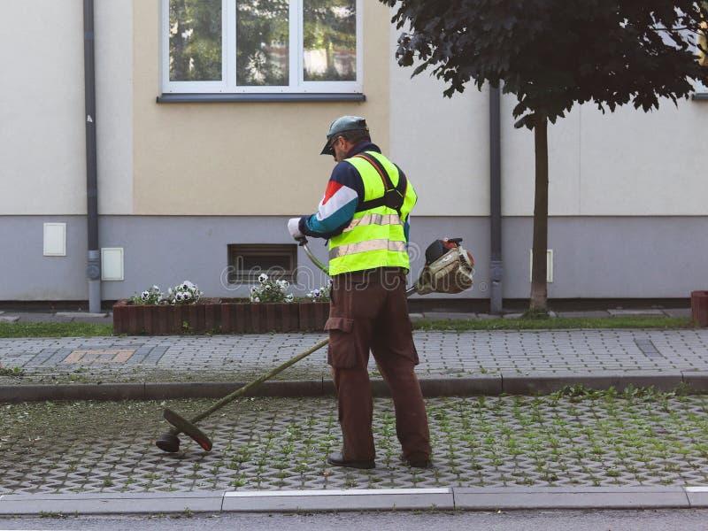 Un empleado del servicio municipal de la ciudad quita el territorio Refinamiento del área alrededor de la casa Siega de la hierba imágenes de archivo libres de regalías
