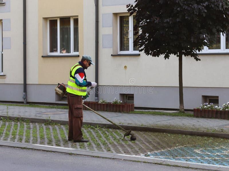 Un empleado del servicio municipal de la ciudad quita el territorio Refinamiento del área alrededor de la casa Siega de la hierba imagenes de archivo