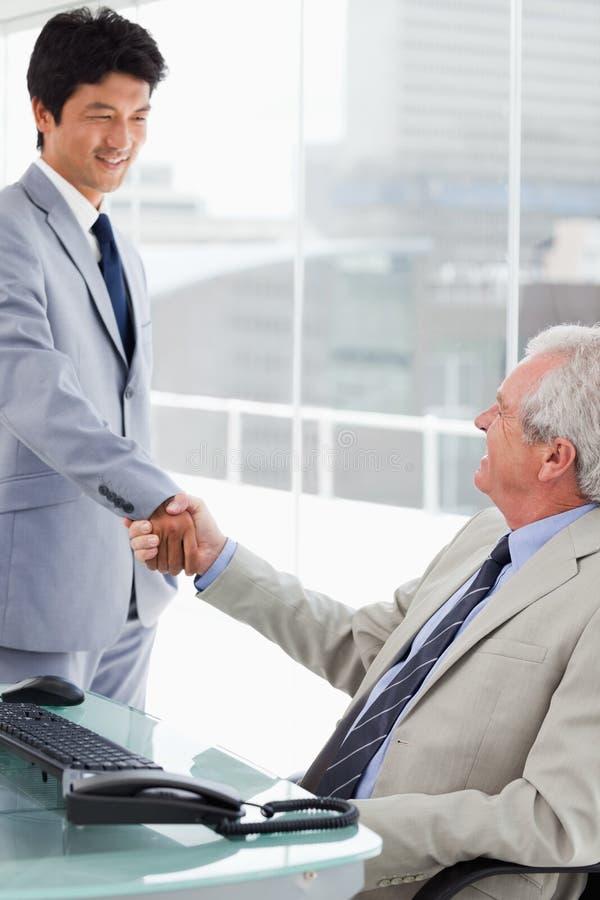 Un empleado sonriente que sacude la mano de su encargado imágenes de archivo libres de regalías