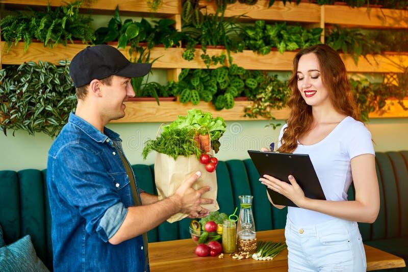 Un employé de messagerie qui livre de la nourriture fraîche à une cliente heureuse qui signe des documents dans la cuisine à la m photo libre de droits