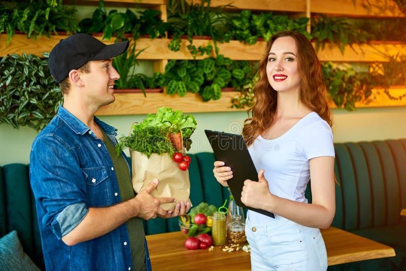 Un employé de messagerie qui livre de la nourriture fraîche à une cliente heureuse qui signe des documents dans la cuisine à la m image libre de droits