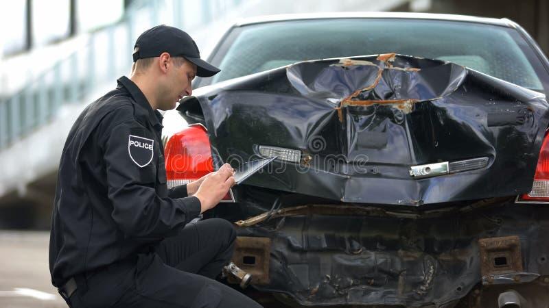 Un employé de patrouille remplissant la tablette se présente en ligne sur les lieux d'une collision avec une voiture, un travail  image stock