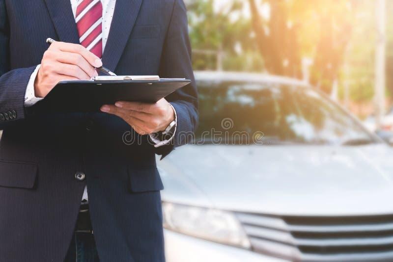 Un employé expert d'assurance travaillant avec une voiture à extérieur photos libres de droits