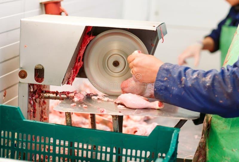 Un employé masculin dans des uniformes coupe la viande sur une scie photo stock