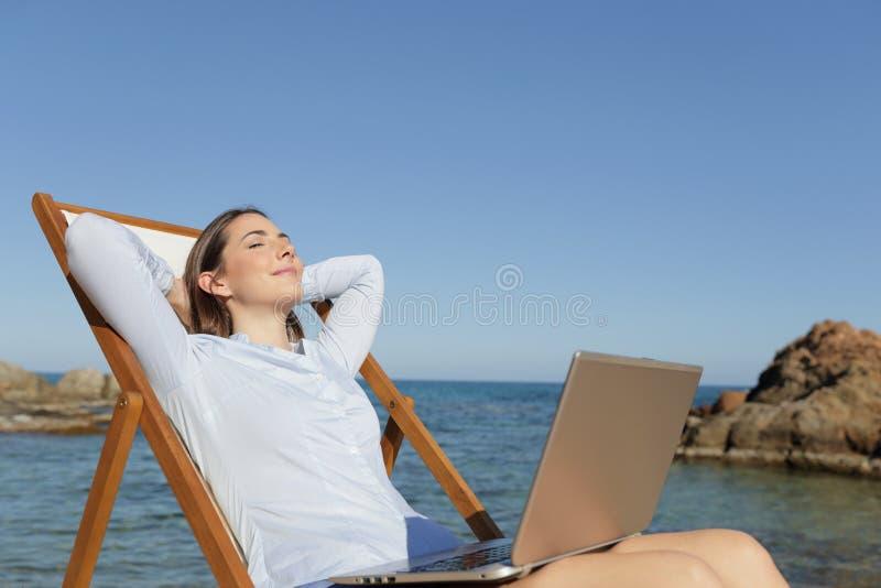 Un empresario relajado descansando en la playa con un portátil foto de archivo libre de regalías