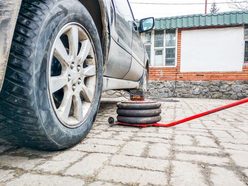 Un enchufe neumático está mintiendo en un suelo de baldosas al lado de un coche polvoriento en un taller de reparaciones del coch imagenes de archivo