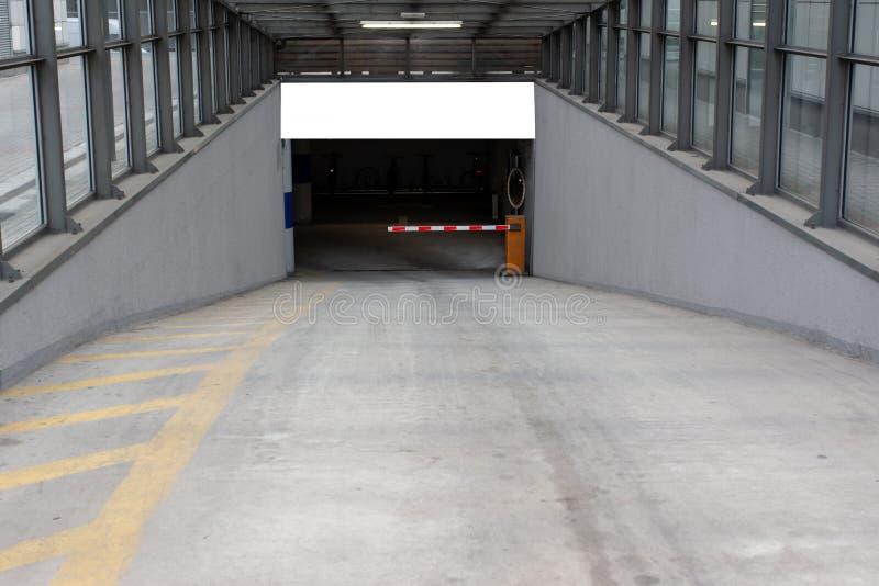 Un endroit d'isolement pour une publicité accrochant au-dessus de l'entrée au garage souterrain photographie stock libre de droits