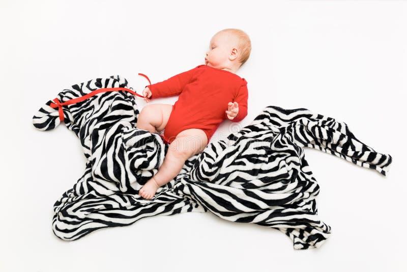 Un enfant âgé de quatre mois monte un zèbre d'un tissu sur le plancher images libres de droits