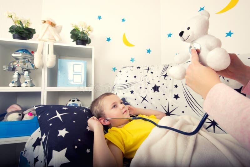 Un enfant écoute un ours de jouet avec un phonendoscope image stock