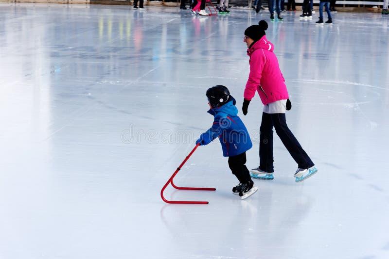 Un enfant apprenant à patiner sur une piste extérieure à Montréal photo libre de droits