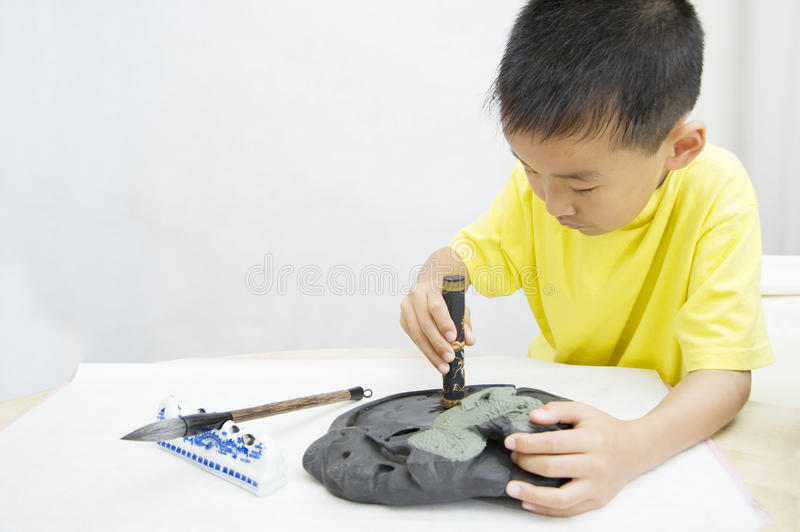 Un enfant apprenant la calligraphie chinoise photo stock