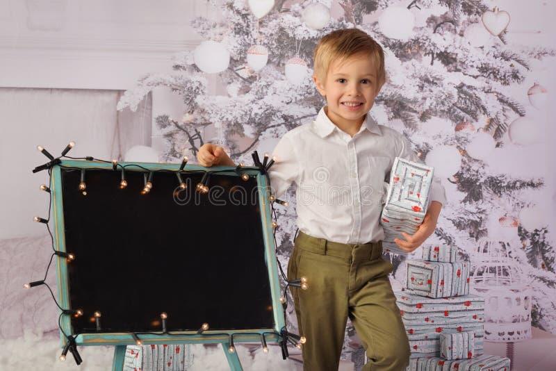 Un enfant avec l'arbre de cadeaux de Noël et de Noël photos stock