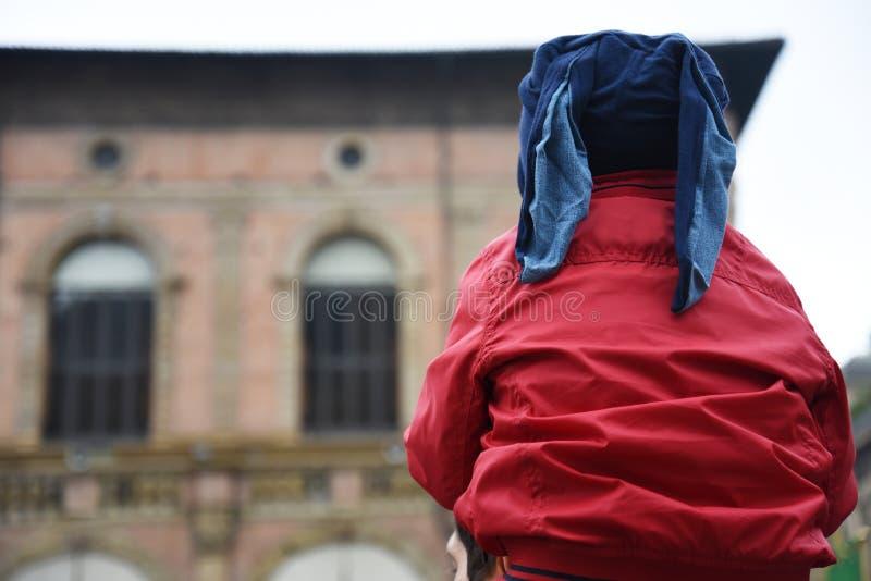 Un enfant avec une veste rouge sont sur les épaules de son père photos libres de droits