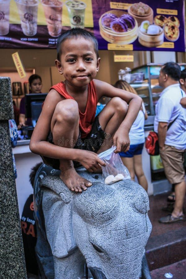 Un enfant ayant son casse-croûte sur la statue d'éléphant images libres de droits