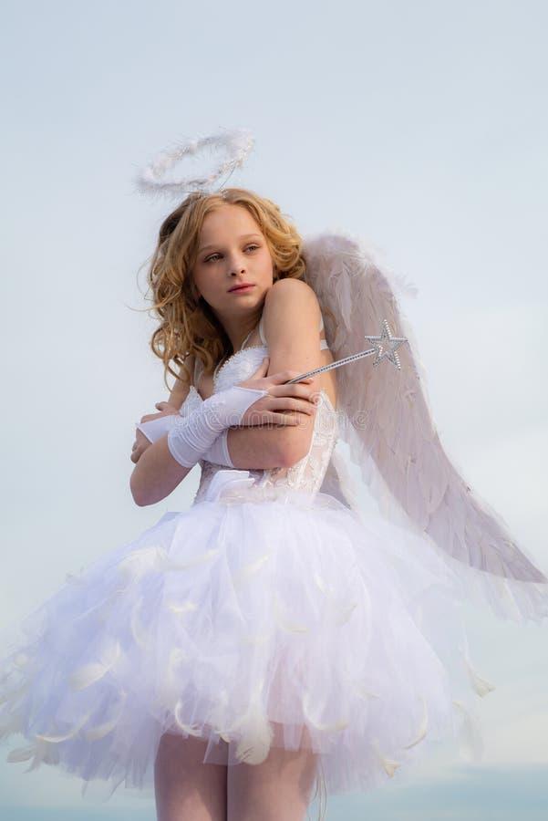 Un enfant dans les v?tements d'un ange sur le fond de ciel - concept de Valentine Enfant avec le caract?re ang?lique Peu d'ange photos stock